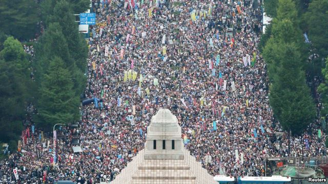 Người dân giơ áp phích và hô khẩu hiệu trong cuộc biểu tình phản đối dự luật an ninh của Thủ tướng Abe bên ngoài quốc hội ở Tokyo, 30/8/2015. Ảnh: REUTERS/Kyodo