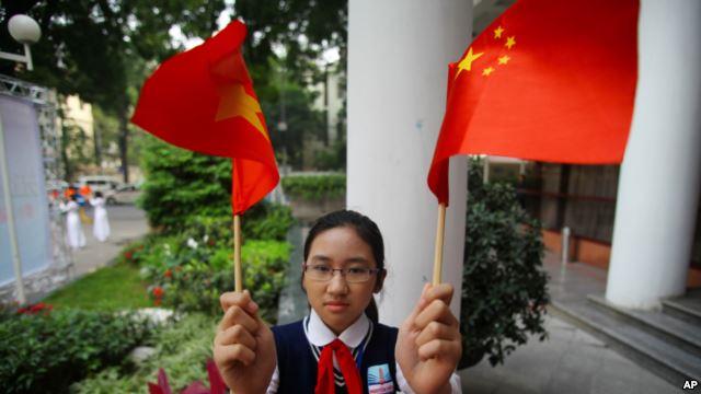 Học sinh Việt Nam cầm cờ Trung Quốc đón ông Tập Cận Bình (ảnh tư liệu).