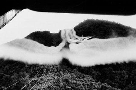 """Máy bay C-123 rải chất diệt cỏ tại các địa điểm đóng quân của bộ đội Việt Nam (""""cộng sản"""") tại một khu vực giữa Sài gòn và Đà lạt tại Miền Nam Việt Nam, 02/8/1963. (Ảnh: Horst Faas/AP Photo)"""