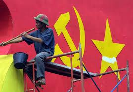 Một công nhân sơn một poster lớn mang cờ đảng cộng sản tại trung tâm Hà Nội.