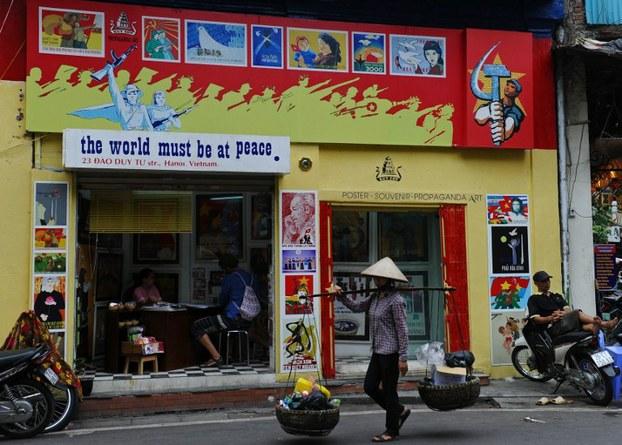 Một người bán hàng rong đi qua một công ty du lịch bán các bản sao áp phích tuyên truyền thời chiến tranh ở Hà Nội hôm 19 tháng 8 năm 2015
