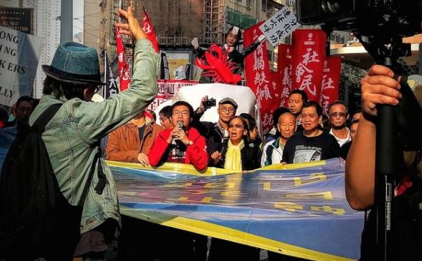 """Một chiếc ô màu vàng - biểu tượng của phong trào dân chủ thành phố - với những người biểu tình mang theo khẩu hiệu """"chiến đấu cho tự do của các thế hệ tiếp theo"""" và đòi hỏi sự từ chức của quan chức """"phản bội"""" thành phố."""