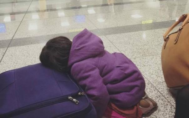 Hình em bé từ Pháp về Việt Nam ăn Tết cùng mẹ. Bé bị sốt nằm gục trên vali quần áo chờ đợi làm thủ tục tại sân bay Nội Bài – (Ảnh: Facebook)