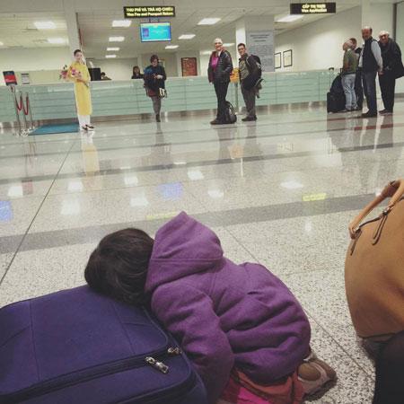 Bức ảnh cô bé bị sốt nằm gục trên vali quần áo chờ đợi làm thủ tục tại sân bay Nội Bài. Ảnh: Facebook