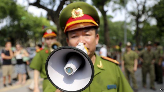 Ảnh minh hoạ: Cảnh sát Việt Nam dùng loa kêu gọi dân chúng và các nhà báo rời khỏi khu vực gần Đại sứ quán Trung Quốc tại Hà Nội, Việt Nam, ngày 18/5/2014.