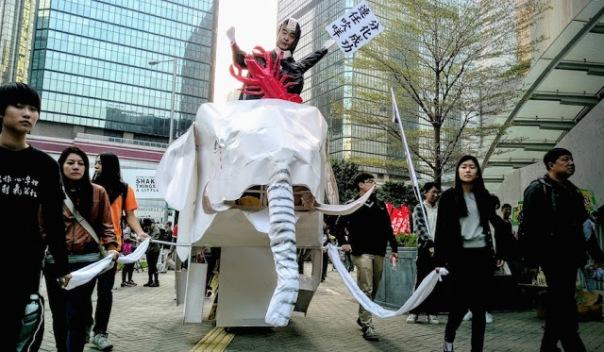 Dẫn đầu các cuộc biểu tình là một bản sao lớn một con voi trắng - tượng trưng cho các dự án đắt đỏ, với mô hình của nhà lãnh đạo không được lòng dân Lương Chấn Anh cưỡi nó.