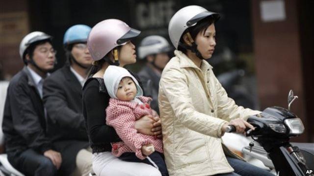 Ảnh minh họa. Trẻ em đi xe không đội mũ bảo hiểm tại Hà Nội.