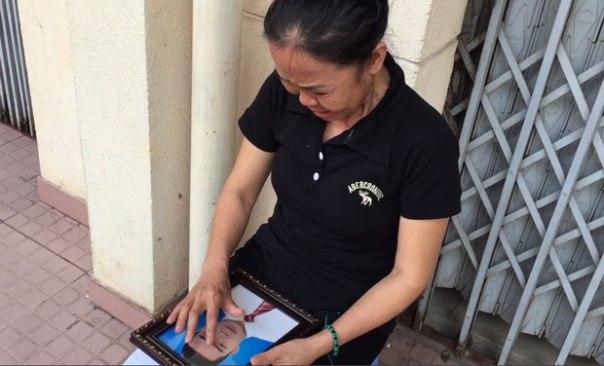 Bà Nguyễn Thị Ái đầm đìa nước mắt ôm di ảnh con trai, anh Phạm Ngọc Nhung.RFA photo