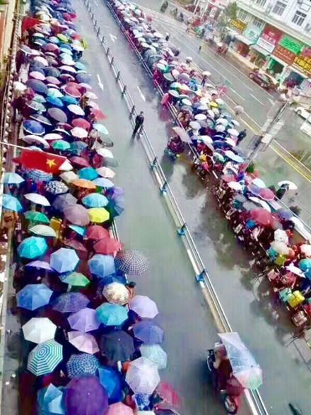 Dòng người xếp hàng dài dưới mưa đợi đến lượt xuất cảnh bên cửa khẩu Đông Hưng. Ảnh: Lao động.