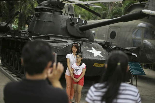 Khách tham quan chụp hình cùng với chiếc xe tăng của quân đội Mỹ, tại Bảo tàng Chứng tích chiến tranh ở thành phố Hồ Chí Minh. Ảnh: japantimes