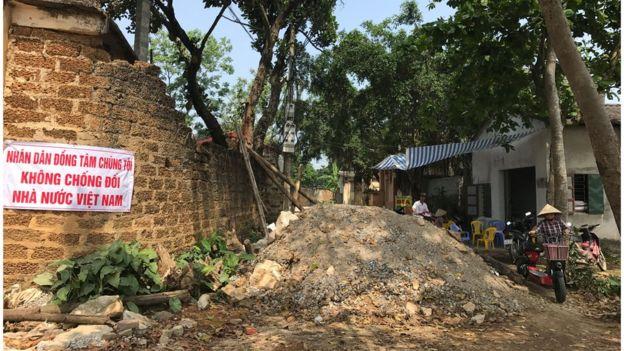 Một biểu ngữ gắn trên tường bên trong xã Đồng Tâm cho hay người dân địa phương 'không chống đối nhà nước'.