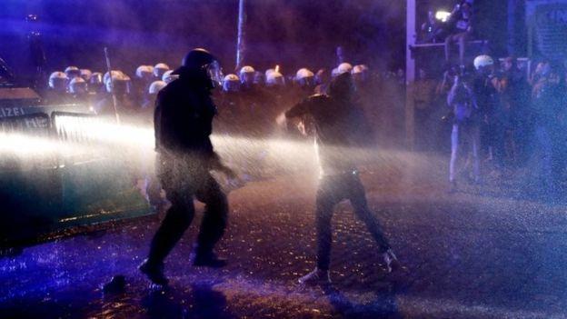 Cảnh sát đã rùng vòi rồng và hơi cay với những người biểu tình bịt mặt ném chai, gạch đá và pháo sáng.